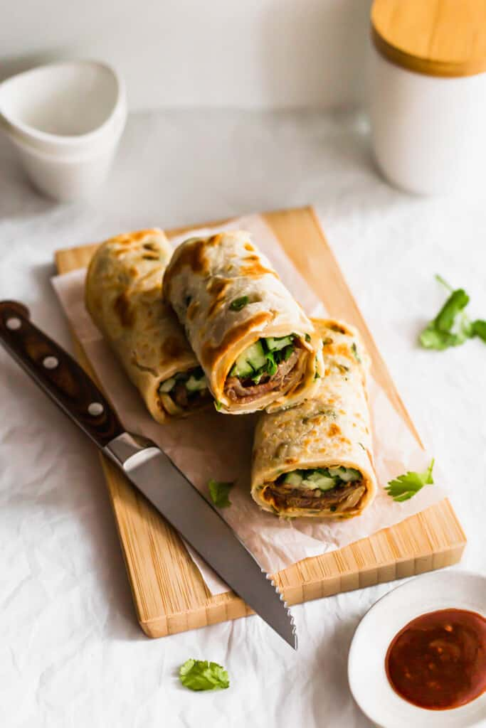 Green onion beef pancake rolls on wooden board with knife.