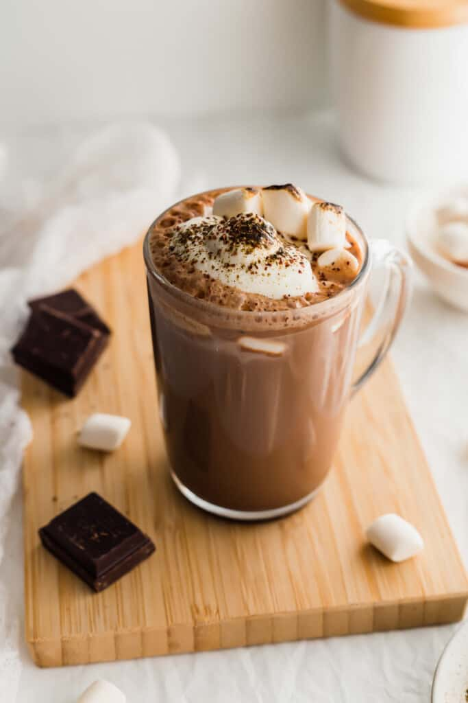 Mug of hot chocolate with whipped cream on wooden board.