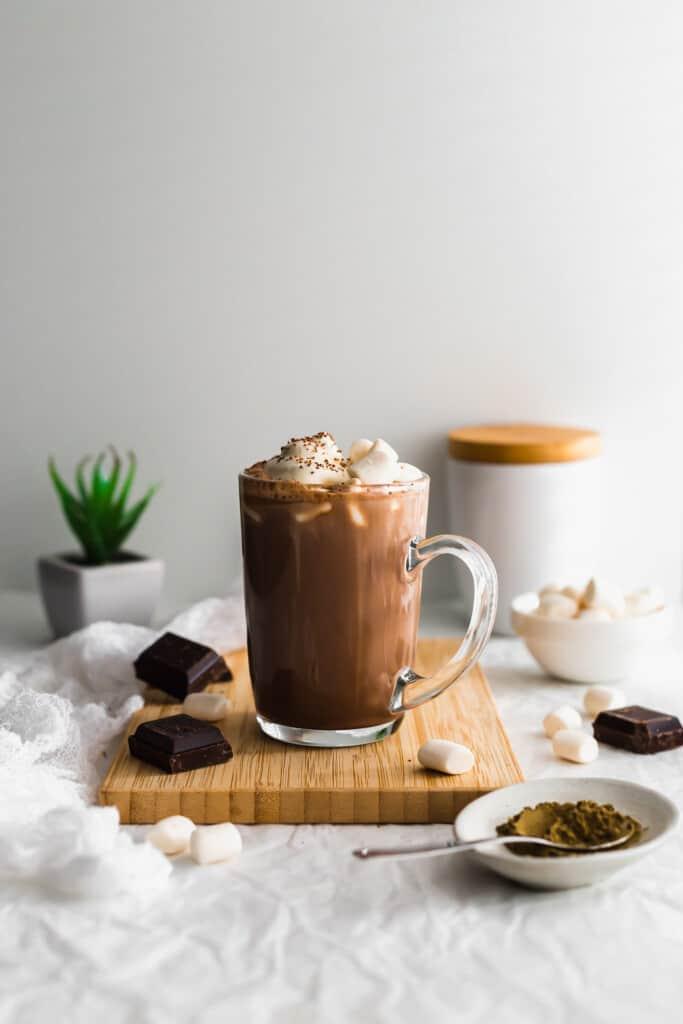 Glass mug of hojicha hot chocolate on wooden board.