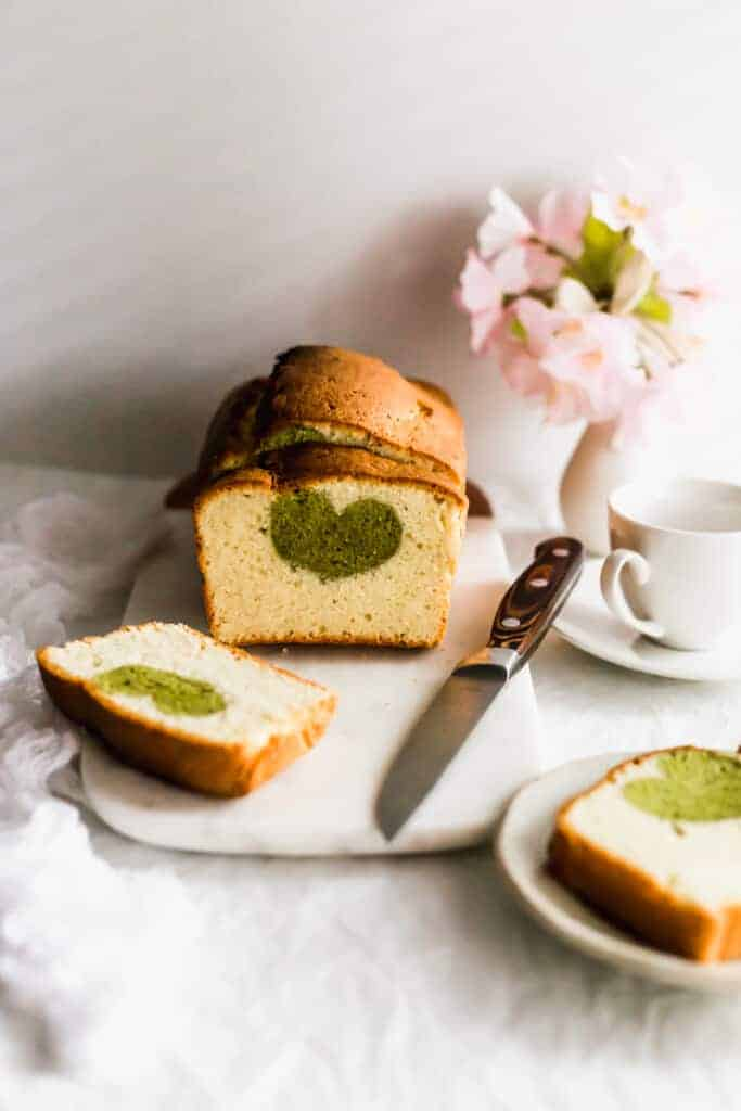 Matcha hidden heart cake on marble board with knife.