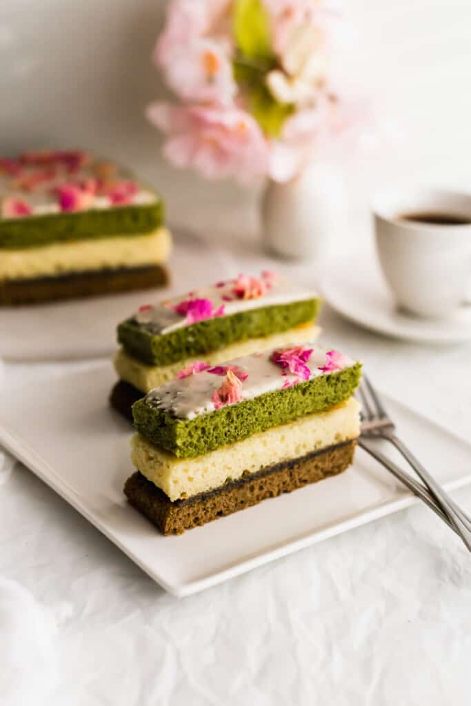 Slices of Matcha Hojicha Vanilla angel cake on white plate with fork.