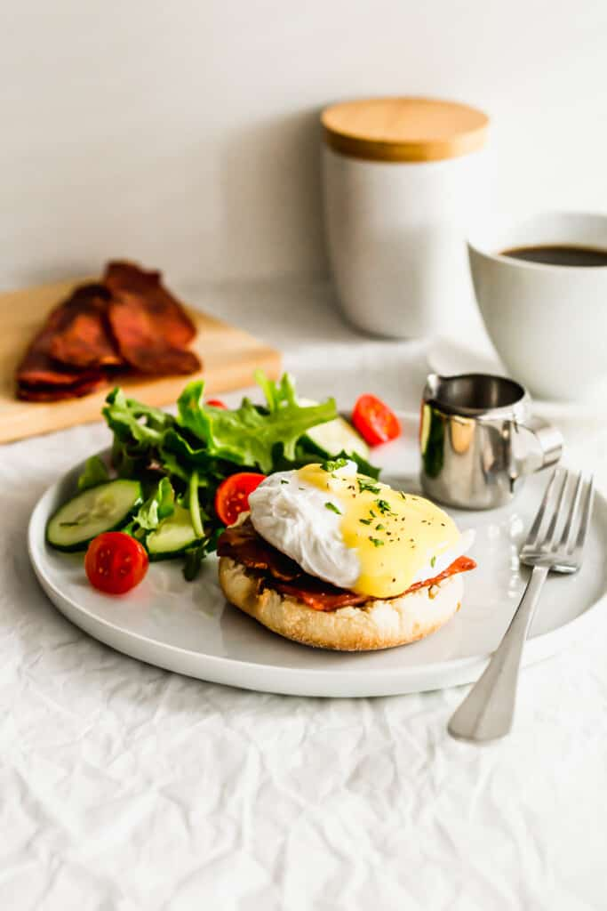 Eggs Benedict on a white plate with salad and fork on side.
