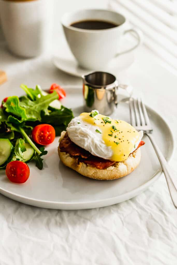 Turkey Bacon Eggs Benedict on a white plate with salad and fork on side.