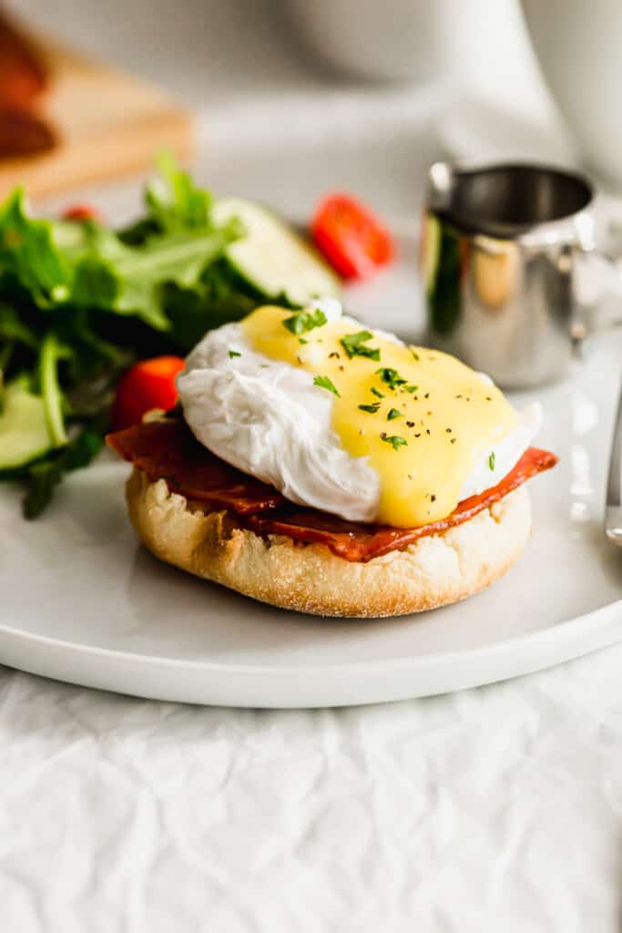 Close up of turkey bacon eggs benedict on white plate.