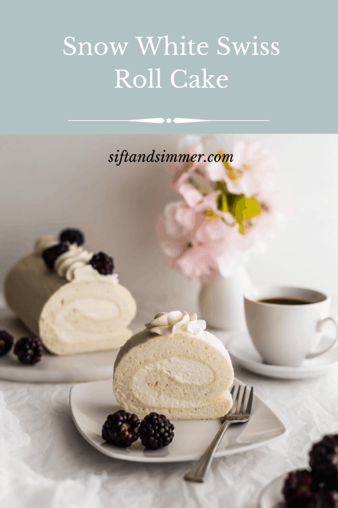 Slice of white roll cake on a plate with blackberries and fork.