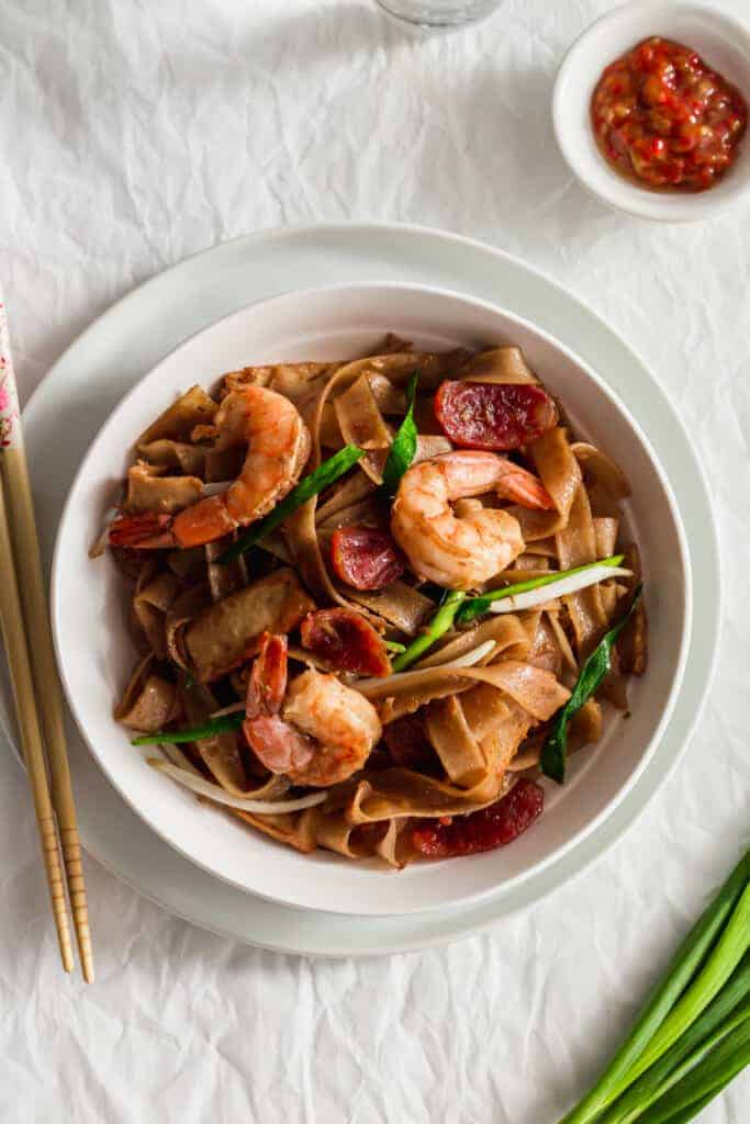 Close up of char kway teow noodles on white plate.