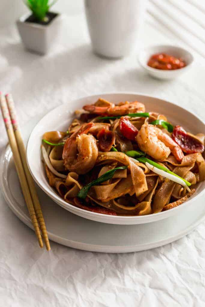 Stir-fried rice noodles in white bowl with chopsticks on side..