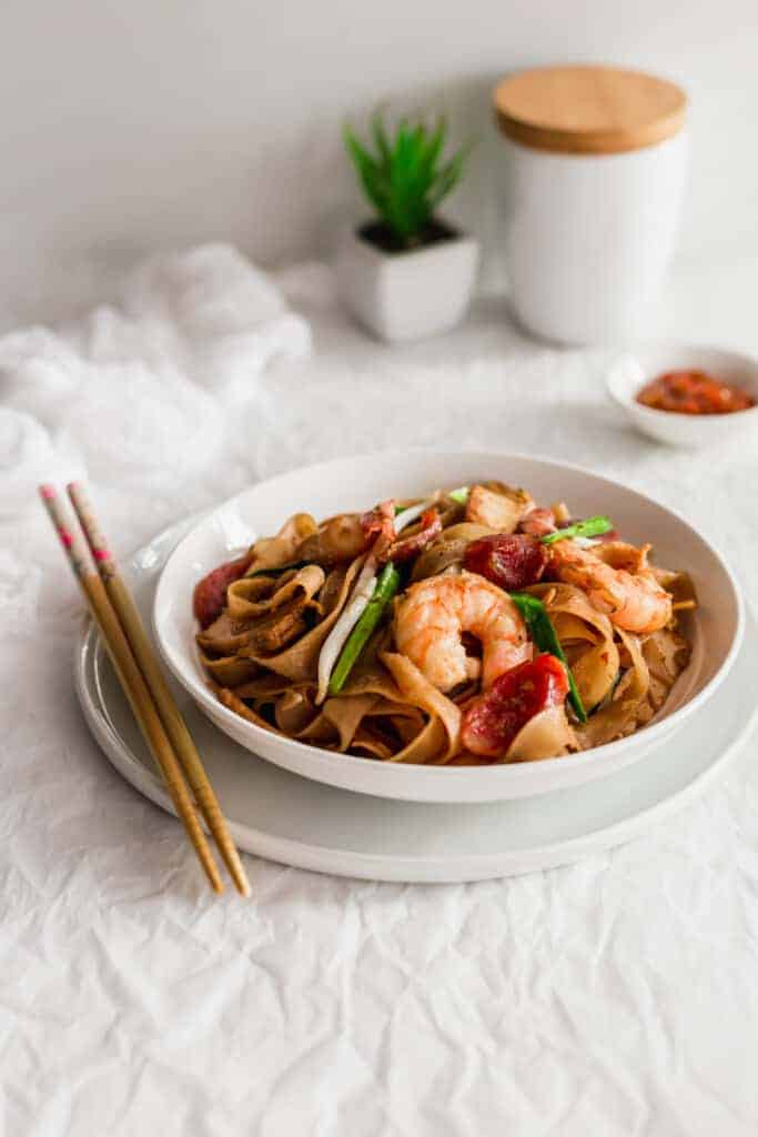 Malaysian Char kway teow noodles in white bowl with chopsticks on side..