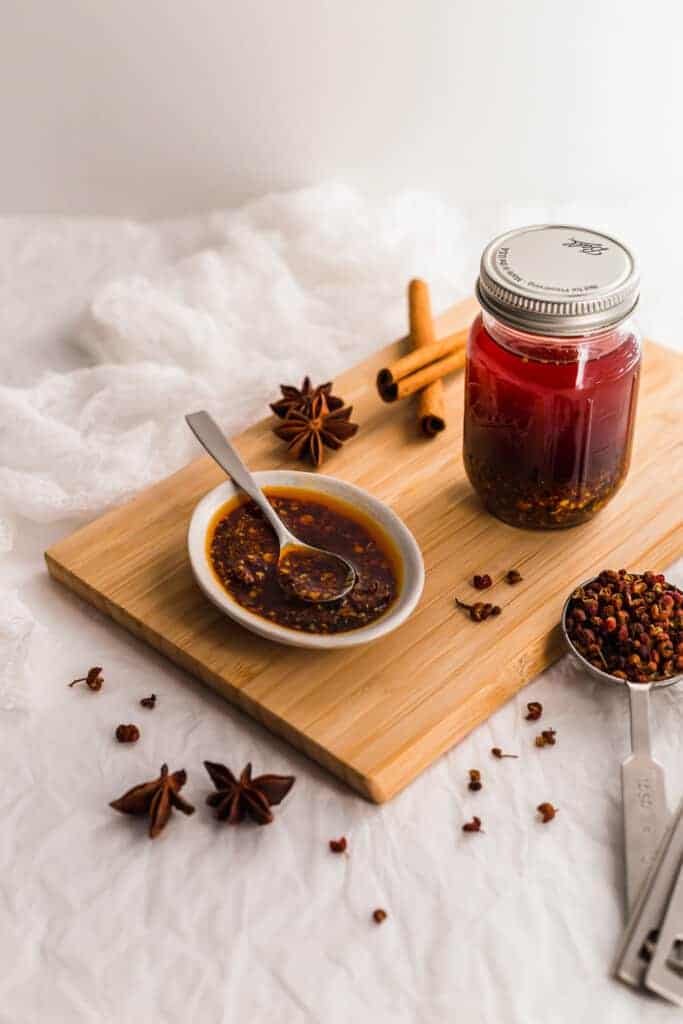 Dish of chili oil with spoon, spices, jar of chili oil on wooden board.