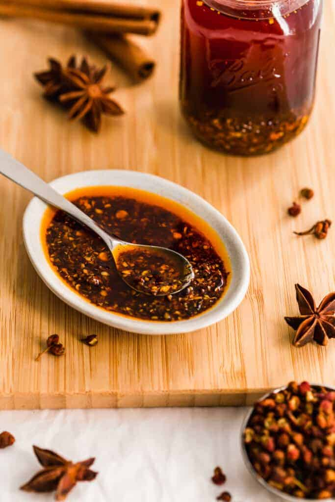 Dish of chili oil with spoon, spices on wooden board.
