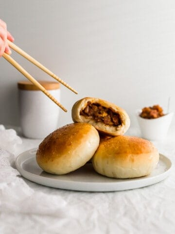 Chopsticks grabbing a torn baked BBQ pork bun on top of other buns on white plate.