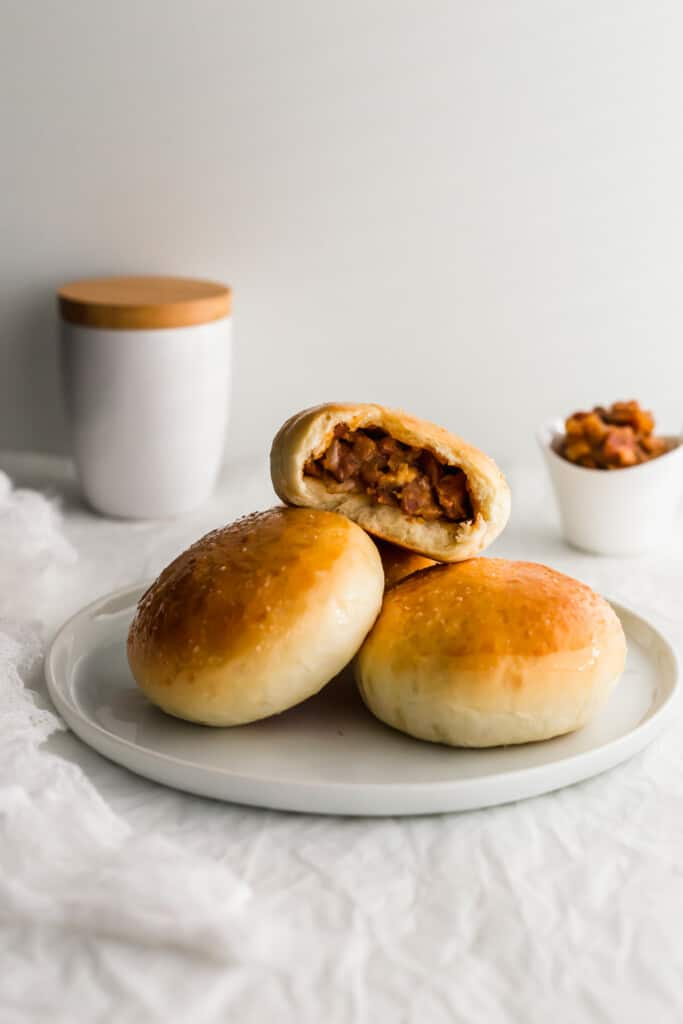 An open baked BBQ pork bun on top of other buns on white plate.