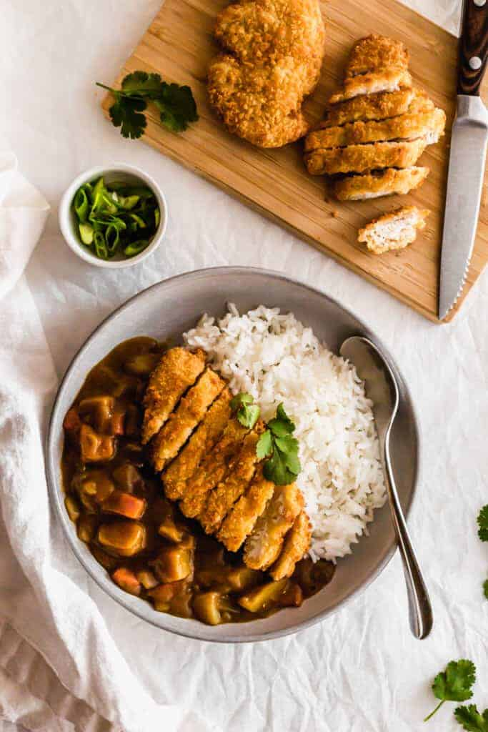 Chicken Katsu Curry with rice on a grey plate with cut up chicken on a wooden board.