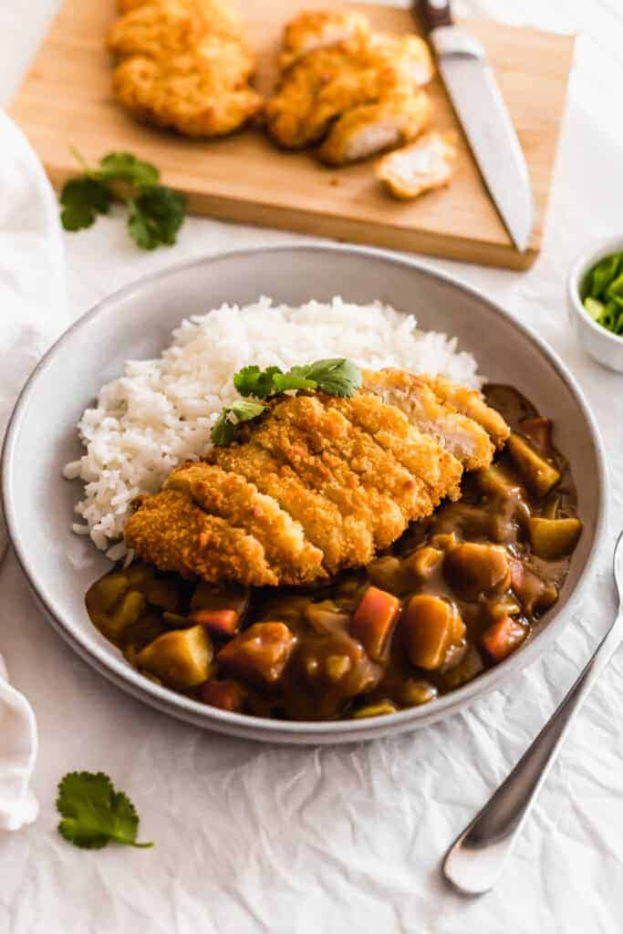 Chicken Katsu Curry with rice on a grey plate.