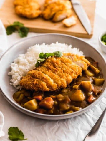 Katsu Curry with rice on a grey plate.