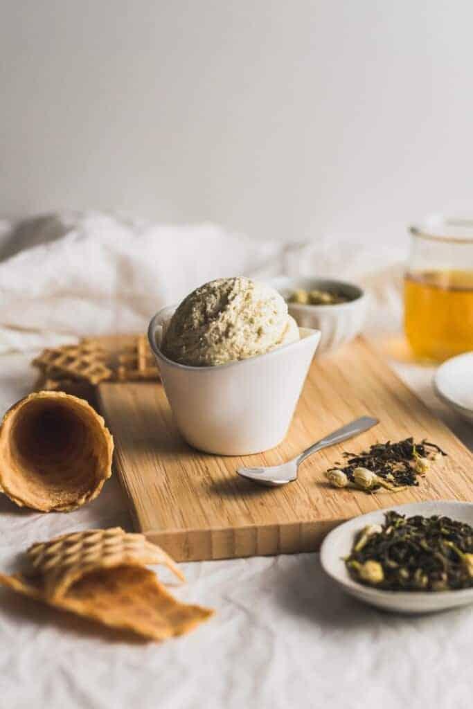 Jasmine tea ice cream in white bowl on wooden board.