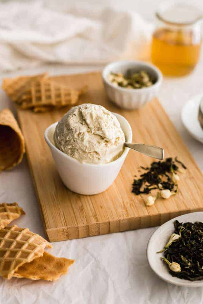 Jasmine tea ice cream in bowl with spoon on wooden board, with jasmine flowers and tea leaves.