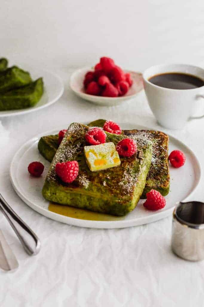 Matcha French Toast with butter and raspberries on a white plate.