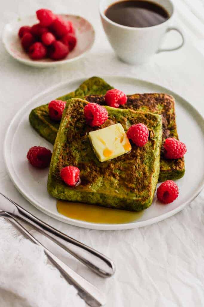 Close up of Matcha French Toast with butter and raspberries on a white plate.