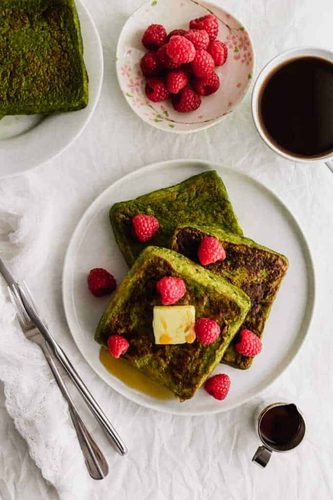 Slices of matcha french toast on white plate with raspberries and a pat of butter.