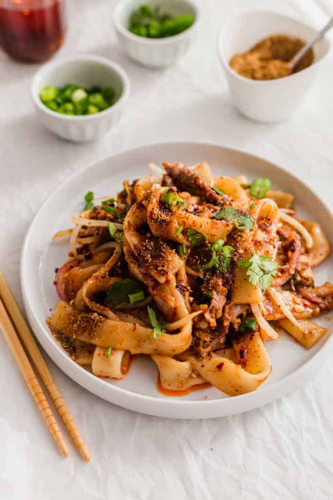 A plate of spicy cumin lamb noodles with chopsticks on side.