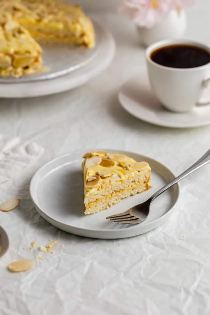 Slice of almond cake with fork on white plate.