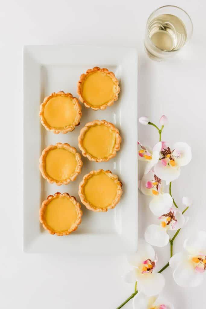 Egg tarts on a white rectangular plate.