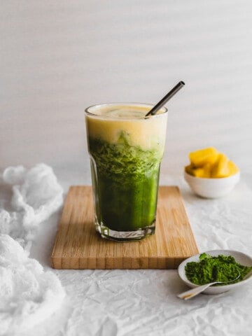 Glass of layered matcha pineapple drink on wooden board.