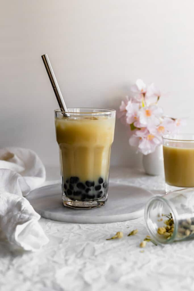 Glass of jasmine milk tea with boba pearls and straw.
