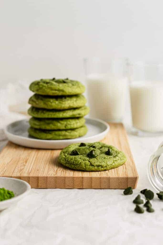 Matcha chocolate chip on a wooden board, with a stack of cookies in the background.