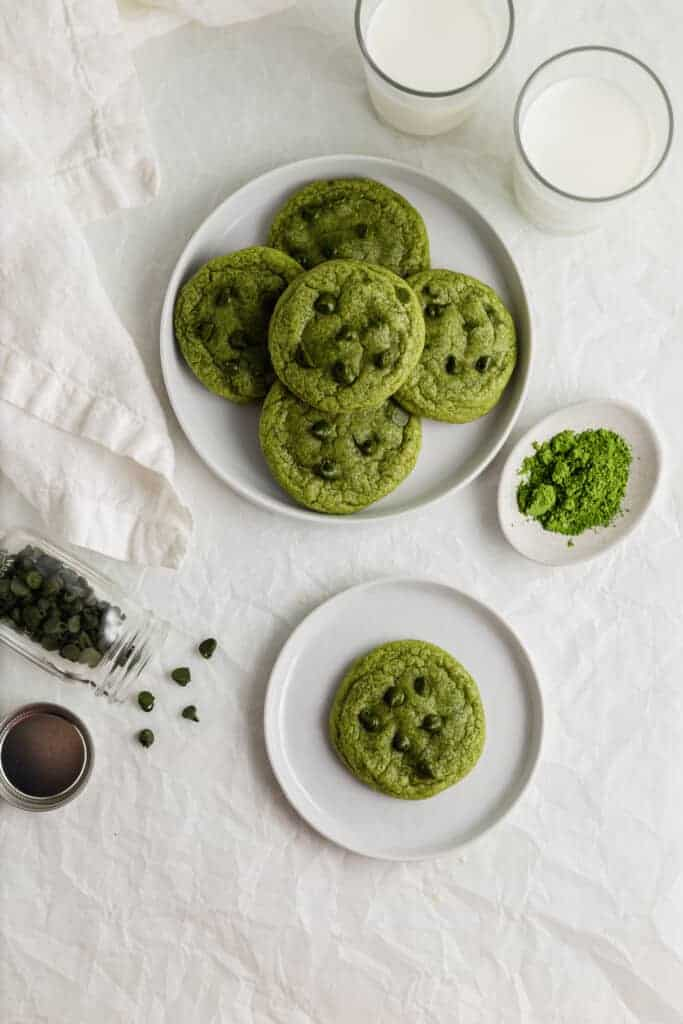 Matcha chocolate chip cookies on white plates with glasses of milk.