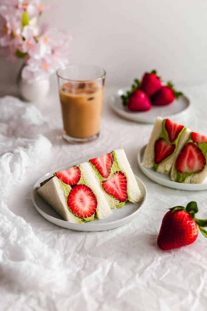 Cut Matcha strawberry fruit sando on plates.