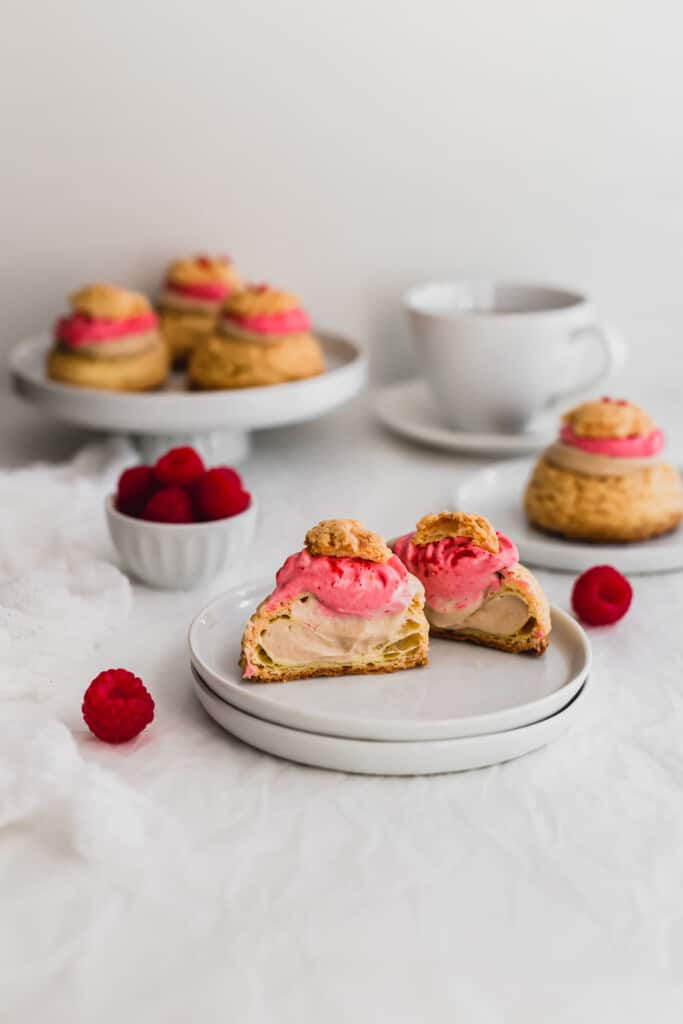 Cut open raspberry earl grey cream puff revealing filling on white plate.