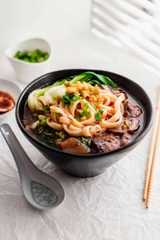 Spicy beef noodle soup in black bowl, with spoon and chopsticks on the side.