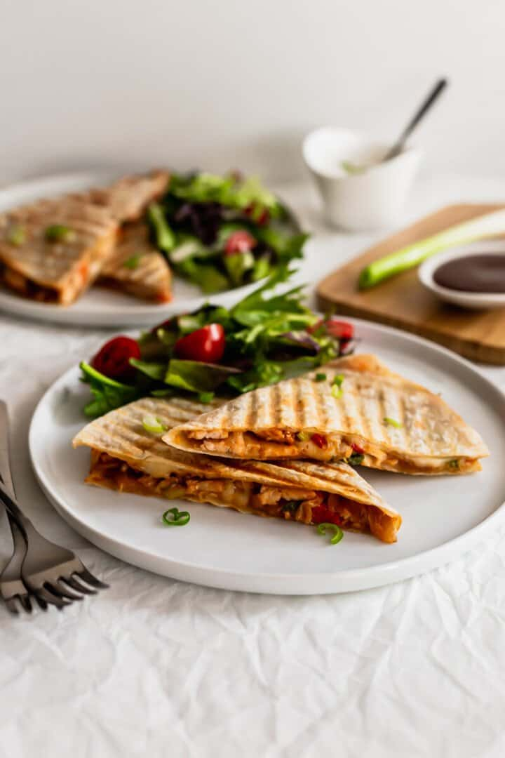 Quesadillas on a white plate with salad.